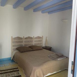 Modelo de dormitorio principal, de estilo de casa de campo, de tamaño medio, con paredes blancas, suelo de baldosas de cerámica y suelo amarillo