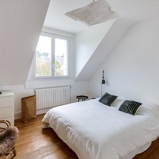 Exemple d'une chambre parentale bord de mer de taille moyenne avec un mur blanc, aucune cheminée, un sol en bois brun et un sol marron.