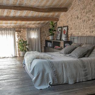 Inspiration pour une chambre parentale méditerranéenne de taille moyenne avec un mur beige, un sol en bois foncé, aucune cheminée et un sol marron.