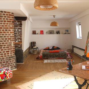 Cette photo montre une chambre parentale éclectique de taille moyenne avec un mur blanc, un sol en bois brun et un sol marron.