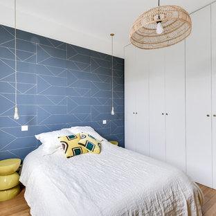 Réalisation d'une chambre tradition avec un mur bleu, un sol en bois clair et aucune cheminée.