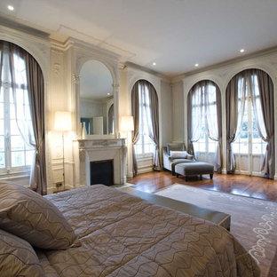 Exemple d'une très grand chambre parentale chic avec un mur beige, un sol en bois foncé, une cheminée standard et un manteau de cheminée en plâtre.