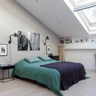 Inspiration pour une chambre mansardée ou avec mezzanine design de taille moyenne avec un mur beige, aucune cheminée, un sol en contreplaqué et un sol beige.