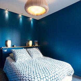 Cette image montre une chambre parentale design de taille moyenne avec un mur bleu, béton au sol et un sol gris.