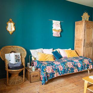 Ejemplo de habitación de invitados campestre, grande, con paredes negras y suelo de madera clara