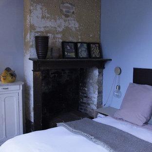 Modelo de habitación de invitados de estilo de casa de campo, de tamaño medio, con paredes azules, suelo de baldosas de terracota, chimenea tradicional y marco de chimenea de madera