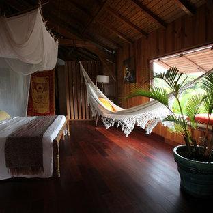Exemple d'une chambre parentale exotique de taille moyenne avec un sol en bois foncé et aucune cheminée.