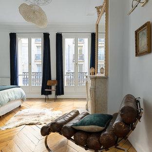 Esempio di una camera matrimoniale scandinava con pareti bianche, pavimento in legno massello medio, camino classico, cornice del camino in pietra e pavimento beige