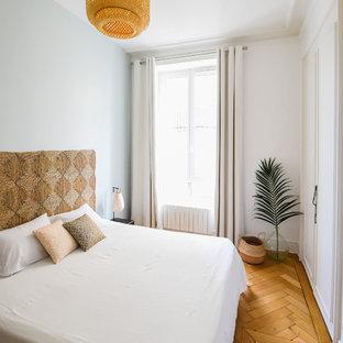 Inspiration pour une petite chambre parentale ethnique avec un sol en bois clair, un mur bleu et un sol beige.