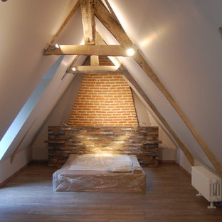 Large country loft-style bedroom in Paris with white walls, dark hardwood floors, no fireplace and brown floor.