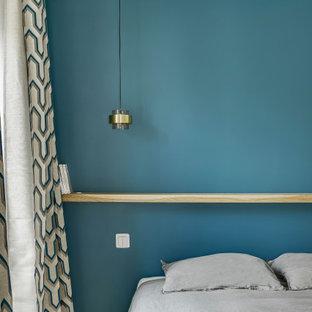 Ejemplo de habitación de invitados urbana con paredes azules, suelo de madera clara y suelo marrón