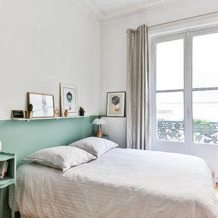 Idées déco pour une chambre parentale beige et marron classique de taille moyenne avec un sol en bois clair et un mur vert.