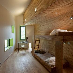 Exemple d'une chambre d'amis montagne de taille moyenne avec un sol en bois brun et un mur blanc.