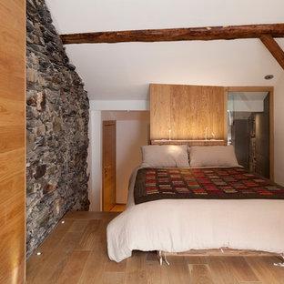 Idée de décoration pour une petite chambre mansardée ou avec mezzanine chalet avec un mur blanc et un sol en bois brun.