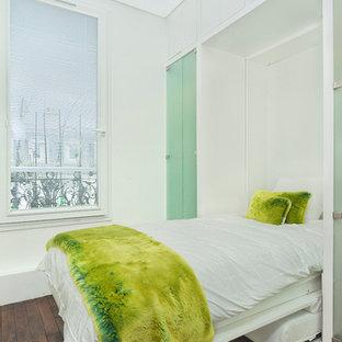 Idée de décoration pour une chambre parentale de taille moyenne avec un mur blanc et un sol en bois brun.