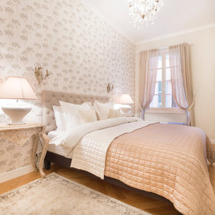 Cette image montre une chambre traditionnelle de taille moyenne avec un mur beige, un sol en bois clair et un sol beige.