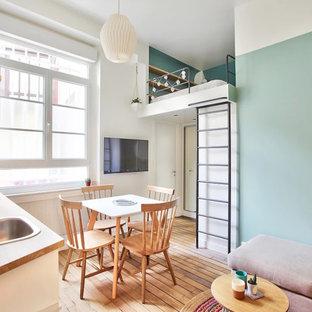 Modelo de dormitorio tipo loft, nórdico, pequeño, con suelo de madera en tonos medios, paredes azules y suelo marrón