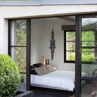 Idéer för ett modernt sovrum, med vita väggar, skiffergolv och svart golv