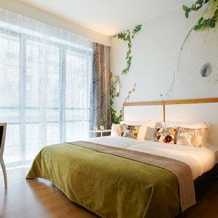 Inspiration pour une chambre parentale design de taille moyenne avec un mur multicolore et un sol en bois brun.