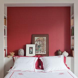 Exemple d'une petit chambre d'amis exotique avec un mur rouge.