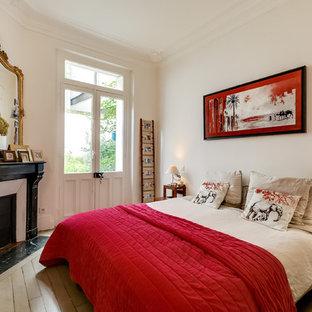 Cette photo montre une chambre parentale éclectique avec un mur blanc, une cheminée d'angle, un sol en bois peint et un manteau de cheminée en pierre.