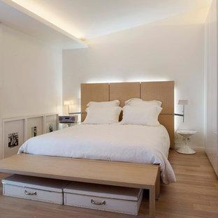 Réalisation d'une petit chambre parentale nordique avec un mur blanc et un sol en bois clair.