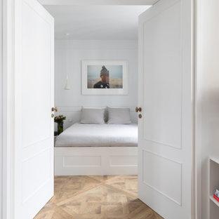 Aménagement d'une chambre contemporaine avec un mur blanc, un sol en bois brun, un sol marron et du lambris.