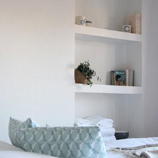 Modelo de dormitorio nórdico con paredes blancas y suelo de baldosas de terracota