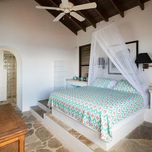 Cette image montre une chambre parentale méditerranéenne avec un mur blanc et un sol gris.