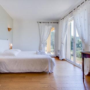Idée de décoration pour une grande chambre d'amis tradition avec un mur blanc, un sol en bois brun et aucune cheminée.