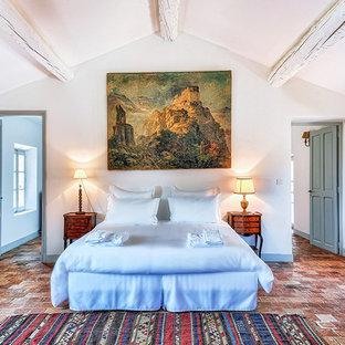 Inspiration pour une chambre parentale méditerranéenne avec un mur blanc, un sol en brique et un sol rouge.