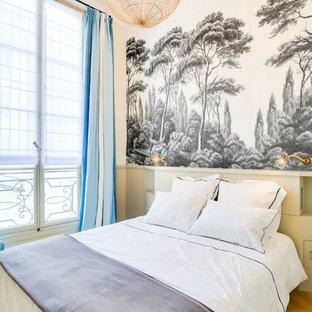 Cette photo montre une chambre d'amis tendance avec un mur blanc, un sol en bois brun et un sol marron.