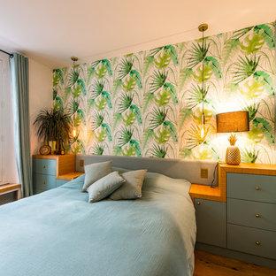 Cette photo montre une chambre parentale tendance de taille moyenne avec un mur blanc, un sol en bois brun, aucune cheminée et un sol marron.