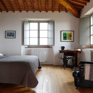 Esempio di una camera da letto mediterranea con pareti bianche, pavimento in legno massello medio e pavimento marrone