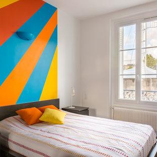 Aménagement d'une chambre parentale contemporaine de taille moyenne avec un mur multicolore, aucune cheminée, un sol en bois foncé et un sol marron.