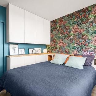 Imagen de dormitorio contemporáneo con paredes azules, suelo de madera clara y suelo beige