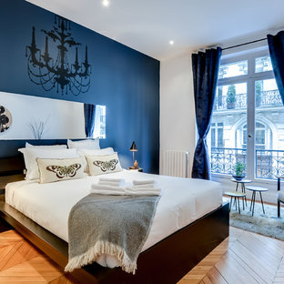 Idées déco pour une grande chambre parentale contemporaine avec un mur bleu et un sol en bois brun.