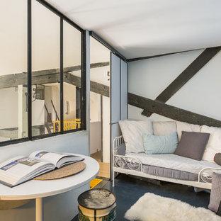 Inspiration pour une chambre mansardée ou avec mezzanine urbaine avec un mur bleu, aucune cheminée et un sol noir.