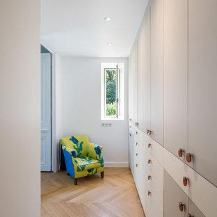 Idee per una piccola camera matrimoniale minimal con pareti bianche, parquet chiaro, camino ad angolo, cornice del camino in cemento e pavimento beige