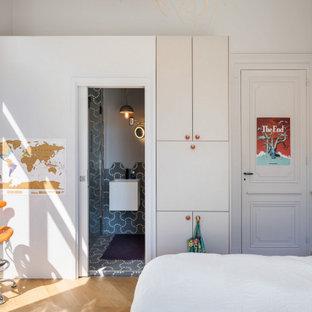 Modelo de dormitorio actual, pequeño, con paredes blancas, suelo de madera clara, chimenea de esquina, marco de chimenea de hormigón y suelo beige