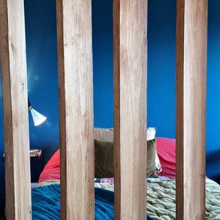 Diseño de dormitorio pequeño con paredes azules, suelo de madera clara y suelo naranja