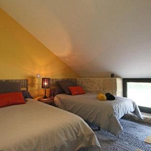 Esempio di una piccola camera da letto stile loft con pareti gialle, moquette e pavimento grigio