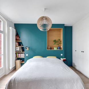 Ejemplo de dormitorio contemporáneo con paredes azules, suelo de madera clara y suelo beige