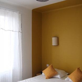 Modelo de habitación de invitados clásica renovada, de tamaño medio, sin chimenea, con paredes amarillas, suelo de contrachapado y suelo marrón