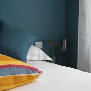 Ejemplo de habitación de invitados clásica renovada, de tamaño medio, sin chimenea, con paredes azules, suelo de contrachapado y suelo marrón