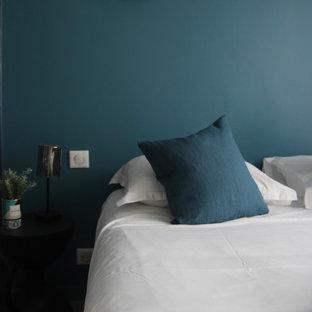 Imagen de habitación de invitados tradicional renovada, de tamaño medio, sin chimenea, con paredes azules, suelo de contrachapado y suelo marrón