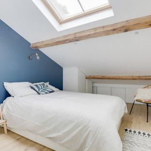 Cette image montre une chambre nordique de taille moyenne avec un mur bleu, sol en stratifié, un sol beige, un plafond en poutres apparentes et un plafond voûté.