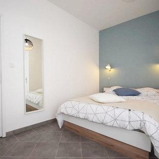 Foto de dormitorio principal, escandinavo, grande, con paredes azules, suelo de baldosas de terracota y suelo gris