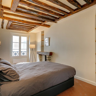 Bedroom - mid-sized traditional loft-style terra-cotta floor and red floor bedroom idea in Paris with beige walls, a standard fireplace and a stone fireplace