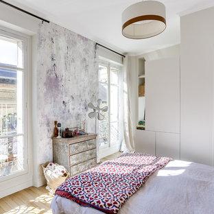 Cette image montre une chambre d'amis design avec un mur blanc, un sol en bois clair et un sol beige.